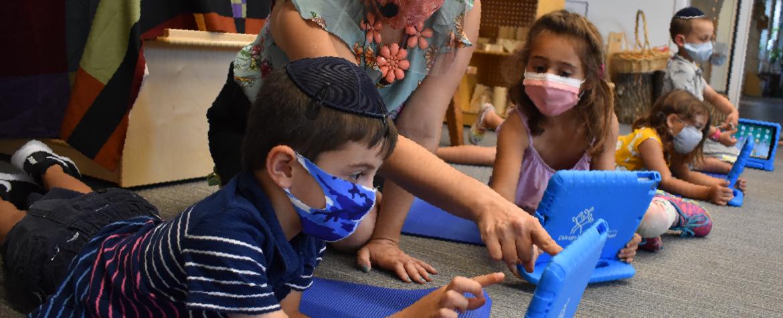Jeunes enfants portant un masque assis par terre avec des tablettes. Éducatrice à genou pointant l'écran d'un jeune élève portant un masque et une kippa.