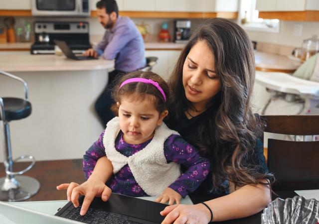 Femme assise à une table de cuisine avec une fillette sur ses genoux. Homme assis en arrière-plan regardant l'écran d'un ordinateur portable