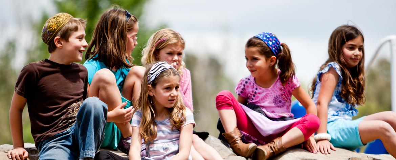 Jeunes enfants assis sur un énorme rocher pendant l'été