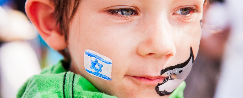 Jeune garçon avec un drapeau israélien et un requin peints sur le visage